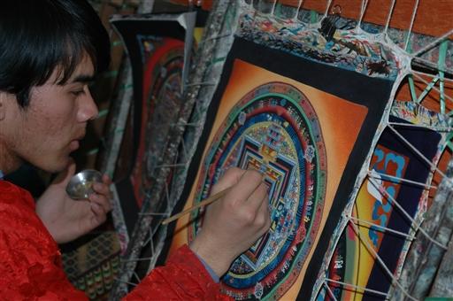 Tibetaner i færd med at male en thanka