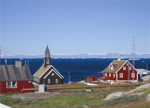 Zions kirken i Ilulissat - Diskoøen ses i horisonten, bemærk den enorme Lyngmarks gletscher, på toppen af fjeldene.