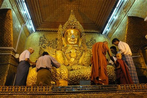 Der lægges bladguld på en af de tusinder Buddhaer.
