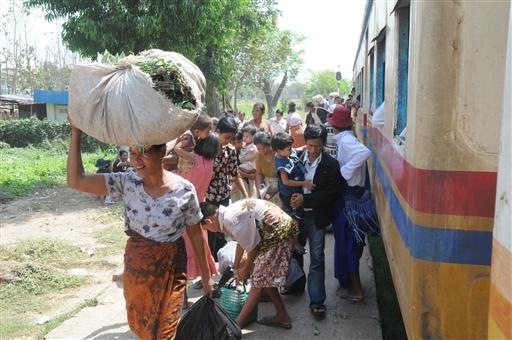 Folk står af og på toget, og køber ind i Yangons landdistrikter