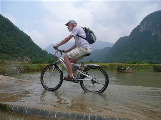 Floden løber over vejen, men det forhindrer ikke en dansk cyklist i at komme videre.