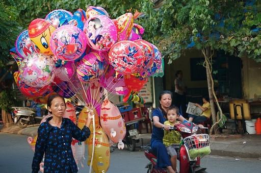 Fest og farver, og den lille dreng med moderen kunne vist godt tænke sig en rød ballon.