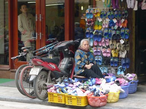Hver dag åbner hun sin egen lille plastsandal-butik i en lille korridor mellem to opgange.