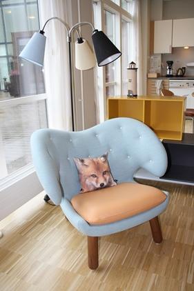 Opholdsstuen med Finn Juhls 'Pelican' stol, og i baggrunden en Montana reol-konstellation i flere farver, som fungerer som rumdeler.