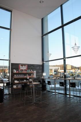 Den enorme loftshøjde giver butikken en fantastisk volume, hvor der samtidig er tænkt over akustikken. Fra café stolene og baren, kan man nyde en go kaffe og kage, samtidig med at man kan følge med i hvad der sker på det travle hjørne udenfor.