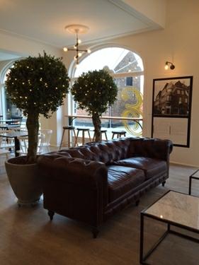 Hyggekrog midt i cafeen med Chesterfield og Marmor borde.