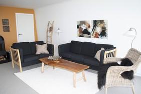 Opholdsstuen, hvor eksisterende sofaer blev genanvendt sammen med mere rustikke møbler