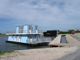Husbåd i Tyskerhavene, Hvide Sande. I samarbejde med Seasight, Hvide Sande. Opgaven bestod i materiale valg, faver, inventar, belysning og møblering. Når man indretter en husbåd er der andre hensyn som skal tages, end ved en 'landbolig'. I dette tilfælde er alle ydervægge fx. inadgående som på en båd. Man skal tage højde for høj søgang hvad fritstående møbler angår, samt lyset og udsigten spiller en stor rolle. Her er der indrettet med traditionelle møbler, med et let udtryk og farveholdningen er skabt af arkitekten på udvendig facade.