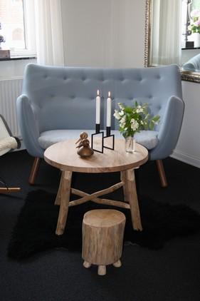 Privat dagligstue, med rustik sofabord og skammel i kontrast til den fine sofa Poeten tegnet af Finn Juhl