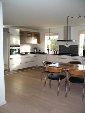Der åbnes op ind til stuen, så der i vinkel dannes et køkken alrum. Det gør begge rum en del lysere, med det gennemgående lys. Hvide klassiske låger/skuffer, gør køkkenet endnu mere lyst, og indretningen gør samtidig at rummet virker meget mere luftigt, samtidig med at både lofter, gulve og vægge ændres til lysere materialer/farver.