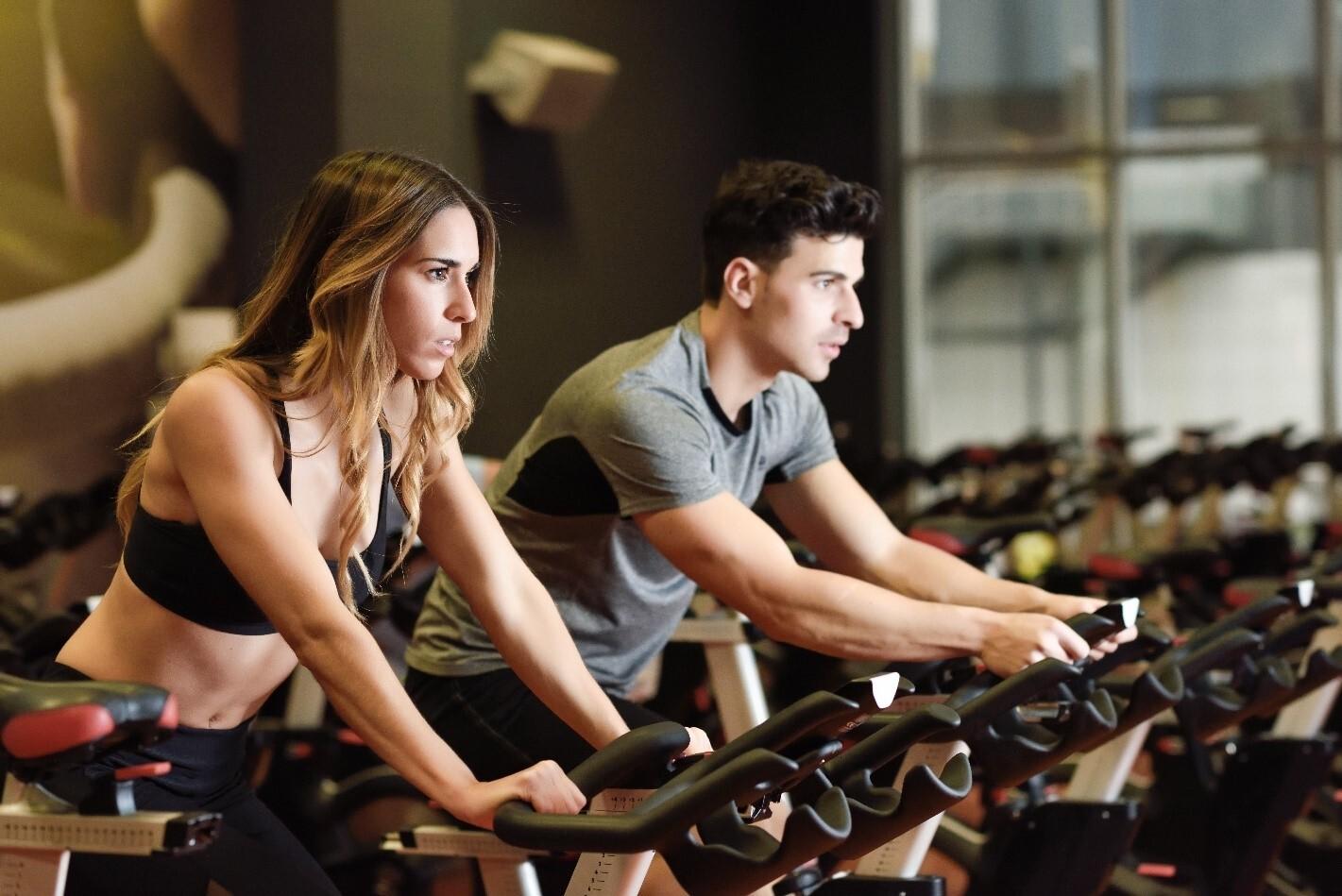 Kvinde og mand på spinningscykel