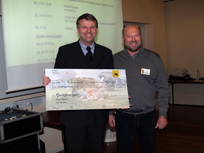 Bestyrelsesmedlem og campingpladsejer Niels Gaj Nielsen overrækker på vegne af DK-CAMP checken på 150.000 kroner til Christian Tramp fra Hjerteforeningen.