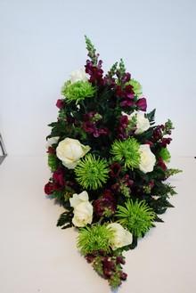 Båredekoration i grøn, hvide og lilla farver.
