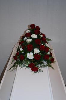 Kistepynt med nelliker og roser.