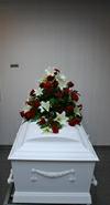 Kistepynt med røde roser og hvide liljer.