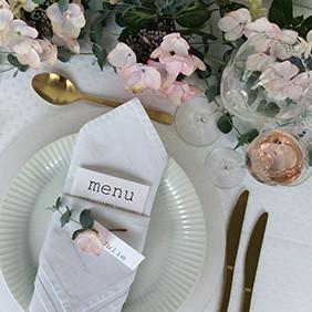 På tallerkenen har vi lagt en enkel men smuk serviet, der er foldet så den får en lomme, hvor man kan placere menuen (eller bestik, bordkort, bordpynt).