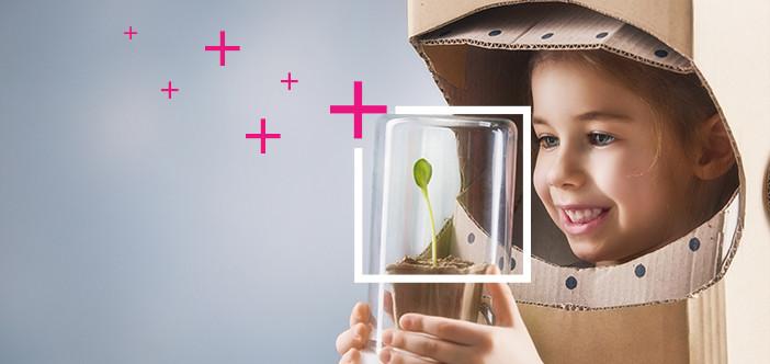 Glad flicka ser med framtidshopp på en liten planta
